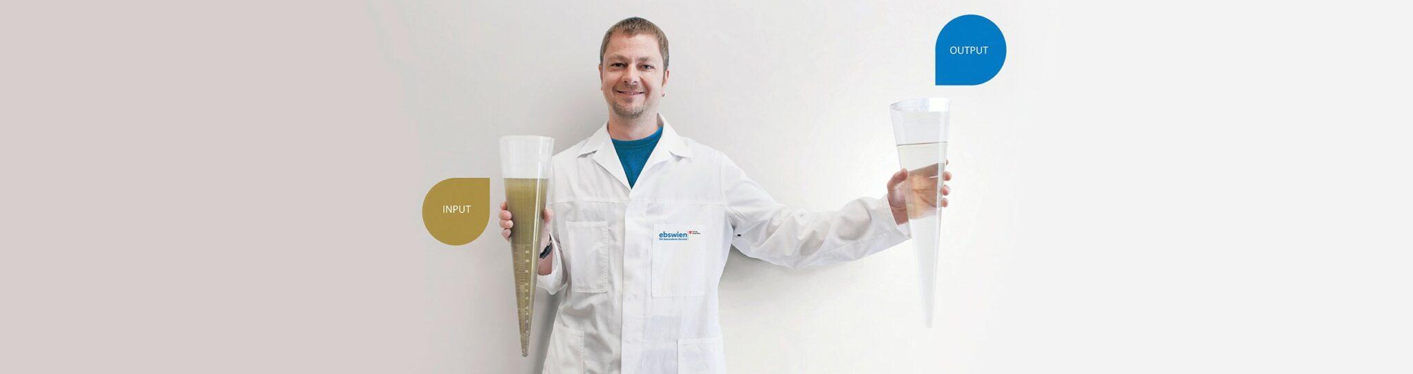 Laborant der ebswien zeigt zwei Imhof-Trichter, von denen je einer mit Rohabwasser und mit gereinigtem Abwasser gefüllt sind. © Christian Houdek