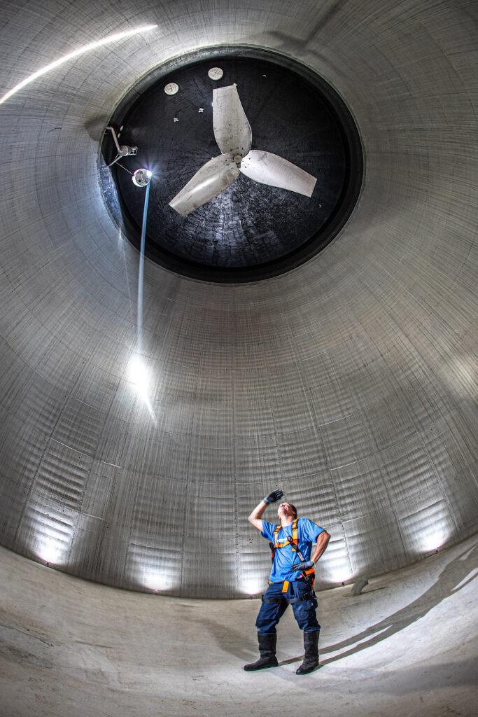 Ein Mitarbeiter der ebswien steht im Inneren eines leeren Faulbehälters und blickt nach oben zum Rührwerk. © Christian Houdek