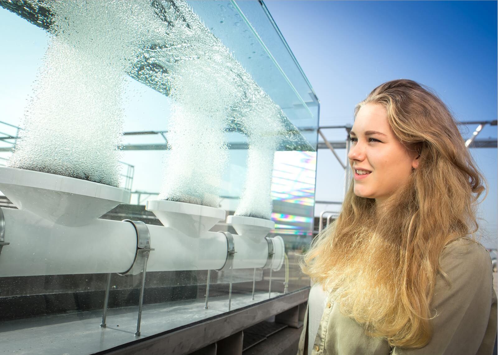 Besucherin vor einem Glaskasten, in dem drei Tellerbelüfter Luftblasen ausstoßen. © Christian Houdek